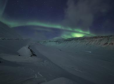 Dog sled in a valley beneath the Northern Lights