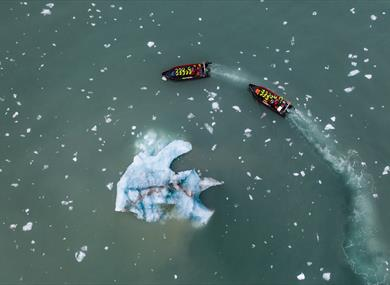 Two RIB boats sailing around an iceberg